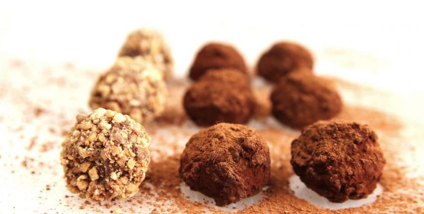 8968705 - nine chocolate truffles with cacao powder on white background
